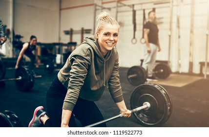 Smiling young woman in sportswear preparing to lift weights during an exercise class in a gym
