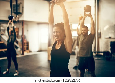 Smiling young woman in sportswear swinging a dumbbell over her head during a gym exercise class