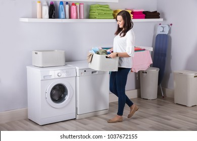 Smiling Young Woman Standing Near Washing Machine With Basket Of Clothes In Kitchen
