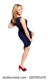 Smiling young woman standing on one leg and looking at camera. Move like a dance. Isolated on white background