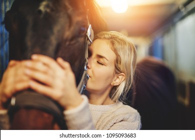 Smiling young woman standing in a stable affectionately hugging her chestnut horse before going for a ride