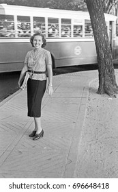 Smiling young woman standing in street with bus driving by