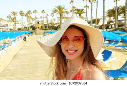 Smiling young woman with straw hat and sunglasses on the beach looking at the camera. Happy beautiful girl with deck chairs, umbrellas and palm trees, typical tropical scenery at Canary Islands, Spain