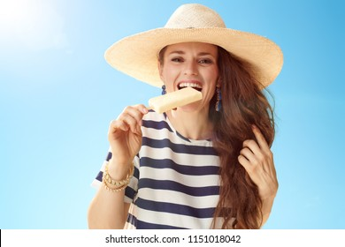 smiling young woman in straw hat against blue sky biting ice cream