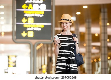 Smiling young woman in straw hat in her 20s waiting for flight in modern airport terminal building, holding mobile phone, looking at screen, using cellphone app or messaging