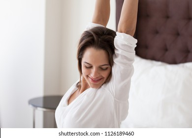 Smiling young woman stretching on cozy comfortable hotel bed in luxury bedroom enjoying good sleep and pleasant weekend morning, feeling fresh and rested starting new day, waking up happy concept