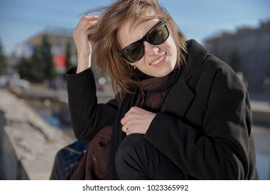 smiling young woman in sunglasses black coat and scarf smiling wide with teeth and squinting from the sun