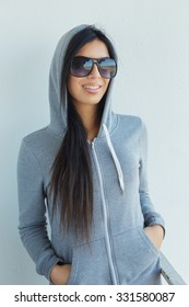 Smiling young woman in sunglasses and grey hoodie.