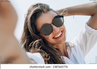 Smiling young woman in sunglasses holding camera and smiling make selfie recording video vlog from hands with mirrorless camera on the beach.Making Vlog, Blogger lifestyle business Concept.