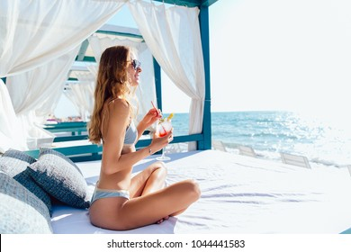 Smiling young woman in sunglasses and swimsuit holds a glass of cocktail, looking at the sea, while sitting on luxury sunbed. On vacation.