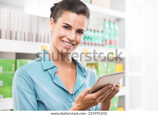 Smiling young woman at supermarket holding a digital tablet with store shelves on background.