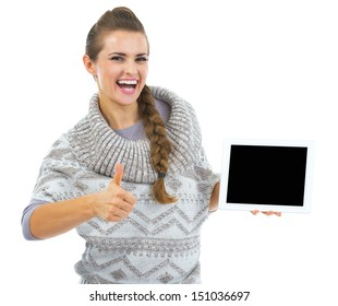 Smiling young woman in sweater with tablet pc blank screen and showing thumbs up