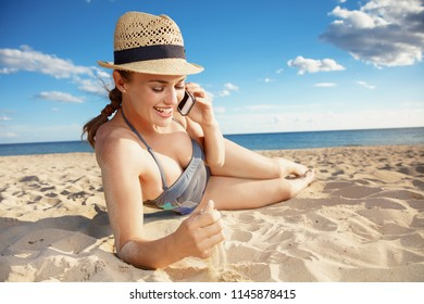 smiling young woman in swimwear on the beach talking on a cell phone