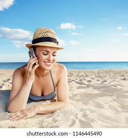smiling young woman in swimwear on the beach using a cell phone