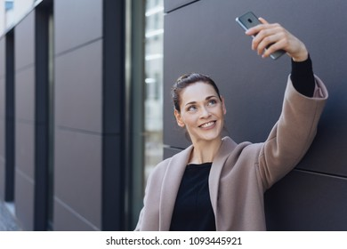 Smiling young woman taking her selfie on her mobile phone as she stands alongside a dark feature wall on a modern building