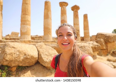 Smiling young woman taking self portrait with greek temple on the background in the Valley of the Temples at Agrigento, Italy