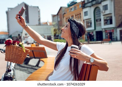 Smiling young woman taking selfie, sitting on a bench on a sunny day, beside the bike with flower basket.