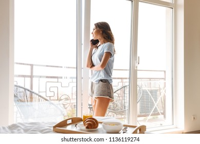 Smiling young woman talking on mobile phone standing at the window while having breakfast in bed