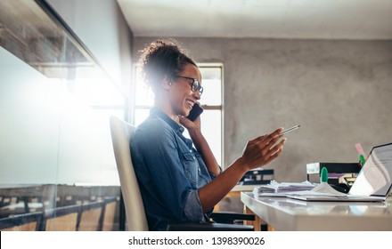 Smiling young woman talking on phone with a laptop in front. Businesswoman in conversation over phone at office.