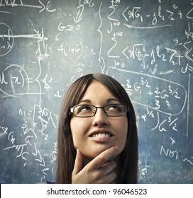 Smiling young woman with thoughtful expression and blackboard in the background