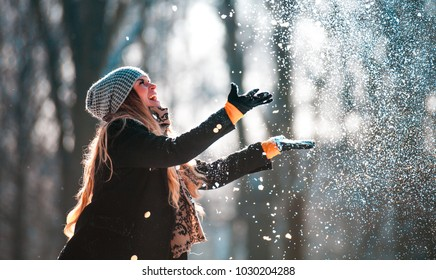 Smiling young woman throwing snow in the air at sunny winter day