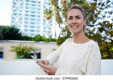 Smiling young woman tourist holding mobile phone in hands while enjoying beautiful day on the street, happy female waiting for text message on cell telephone while resting outdoors in spring weekend