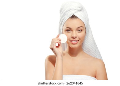 Smiling young woman with a towel on her head, healthy pure skin and removes makeup from the face with cotton pad on white background