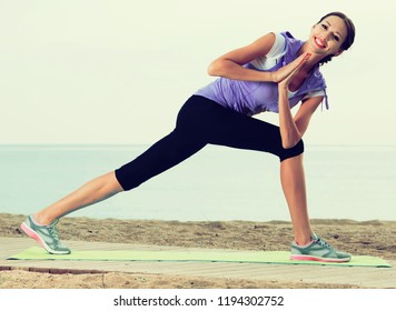 Smiling young woman training yoga asanas standing on beach on sunny morning