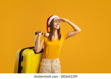 Smiling young woman traveller with red Santa hat carrying big suitcase and looking at copy space, yellow studio background. Happy lady travelling while Christmas and New Year, active winter holidays