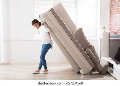 Smiling Young Woman Trying To Move Large Sofa At Home