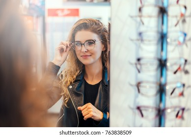 Smiling young woman trying on glasses on mirror in optician.