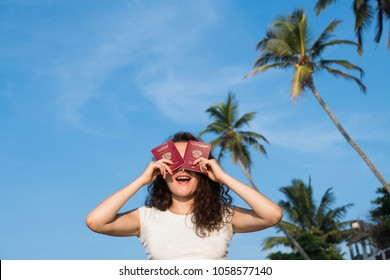 Smiling young woman with two russian foreign passports closing eyes with palms against the blue sky