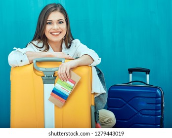 Smiling young woman with two suitcase shows thumb up. Blue wall back.