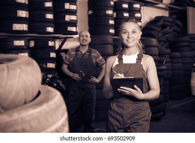 smiling young woman in uniform standing and writing down data in auto workshop