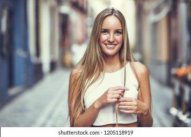 Smiling young woman in urban background. Blond girl wearing with nice hair casual clothes in the street. Straight hairstyle.