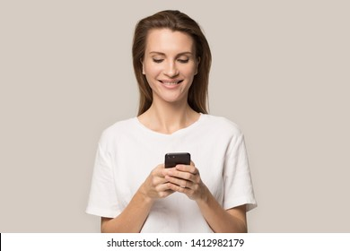 Smiling young woman using cellphone apps, attractive female looking at mobile device screen, girl chatting online in social network, reading good news, message, isolated on studio background