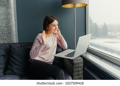 Smiling young woman using laptop and making video call in cafe.