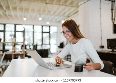 Smiling young woman using laptop and playing with slinky in bright office.