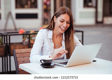 Smiling young woman using laptop in the cafe outdoors.