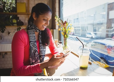 Smiling young woman using phone at window sill in cafe