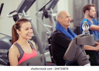Smiling Young Woman Using Recumbent Exercise Bike in Busy Gym