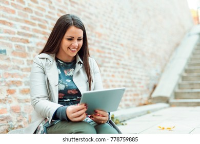 Smiling young woman using tablet in front of brick wall