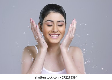 Smiling young woman washing face with water over gray background