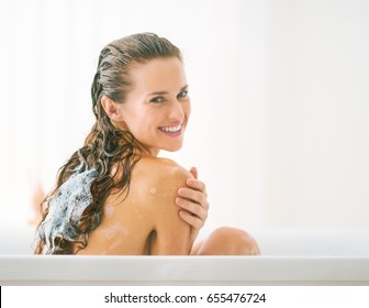 Smiling young woman washing hair in bathtub