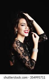 Smiling young woman wearing a classic black lace dress and crystal jewelery with hands up in her hair.  Shot on black background.