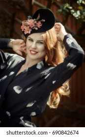 Smiling young woman wearing floral vintage dress and hat