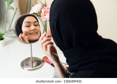 smiling young woman wearing makeup and hijab