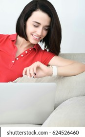 Smiling young woman wearing smartwatch lying on couch and using laptop
