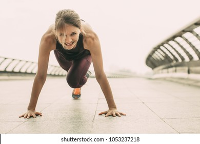 Smiling young woman wearing sportswear, looking at camera and doing mountain climber exercise. Front view.