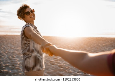 Smiling young woman wearing sunglasses playfully leading her girlfriend by the hand along a sandy beach at sunset